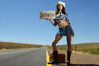 Woman hitchhiking with sign saying 'South'